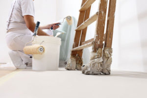painter crouched beside bucket and ladder with roller in hand